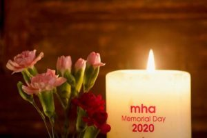A lit candle with MHA Memorial Day 2020 written on it next to a small bunch of flowers
