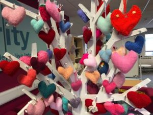 A wooden tree decorated with colourful knitted hearts